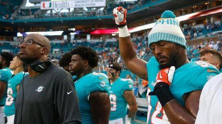 Dolphins defensive end Robert Quinn raises his right