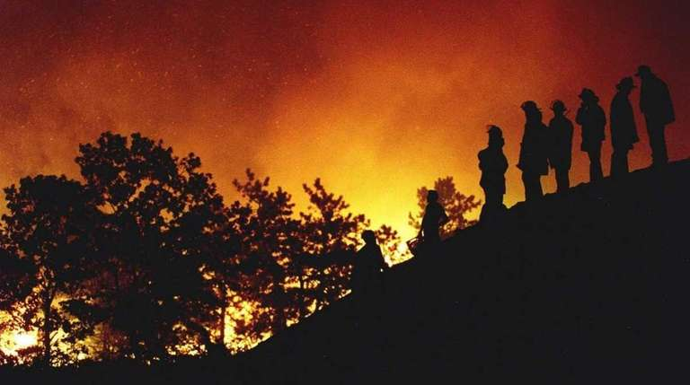 Firefighters survey the Sunrise Fire on Aug. 25,