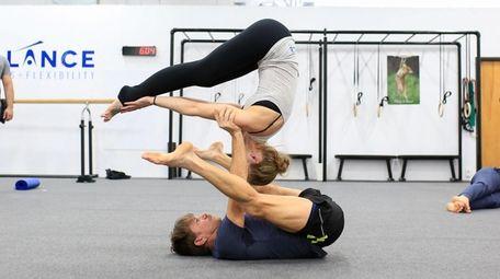 Gene Feis and and Regina McGowan practice acro-yoga