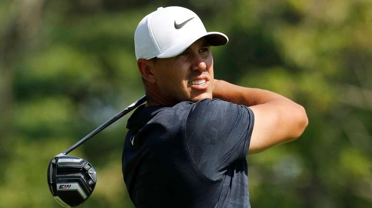 Brooks Koepka watches his shot from the fourth