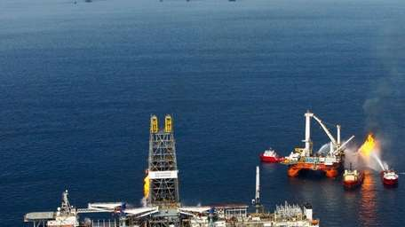 The Discoverer Enterprise drillship, left, burns off gas