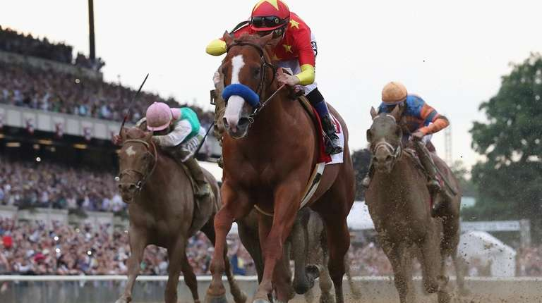 Justify, ridden by Mike Smith crosses the finish