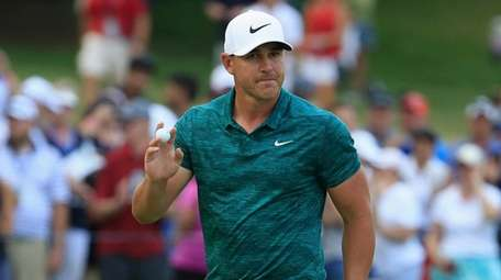 Brooks Koepka reacts after making a putt for