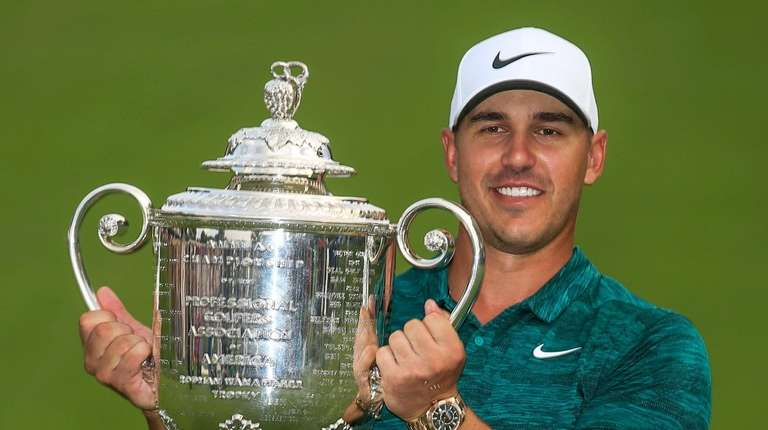 Brooks Koepka poses with the Wanamaker Trophy after
