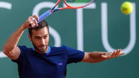 Noah Rubin returns a ball to Fabio Fognini