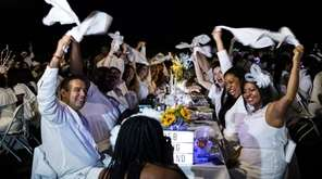 "White-garbed revelers do the traditional ""napkin twirl"" to"