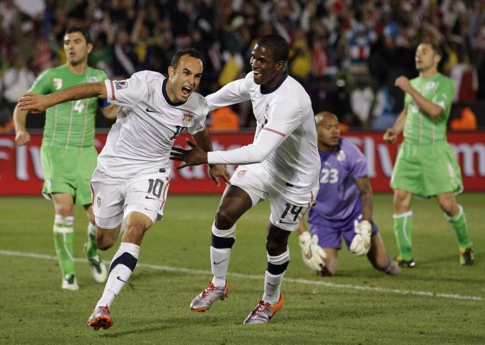 Landon Donovan, left, celebrates after scoring a last-minute