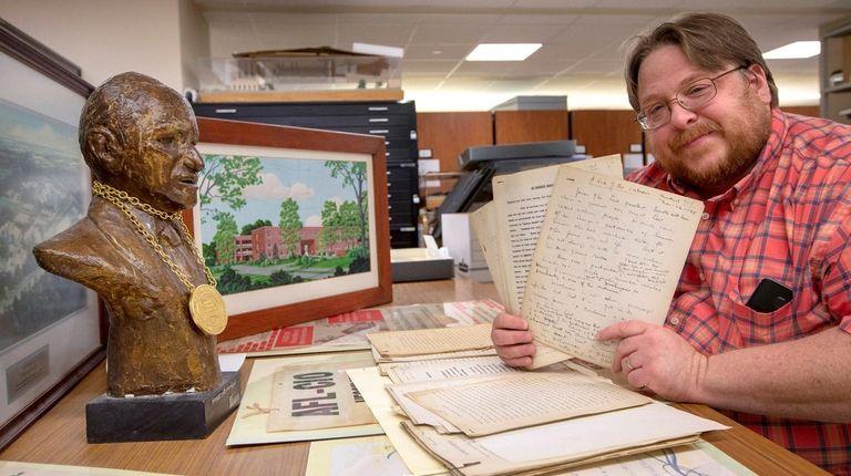 Adelphi University archivist David Ranzan shows items from