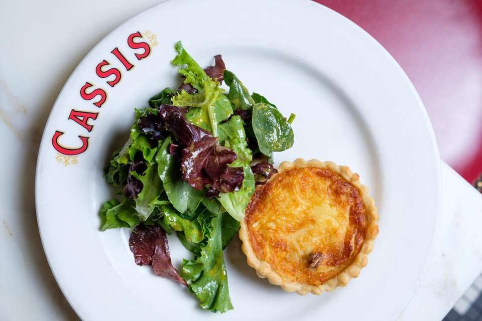 Quiche lorraine served with a side salad at