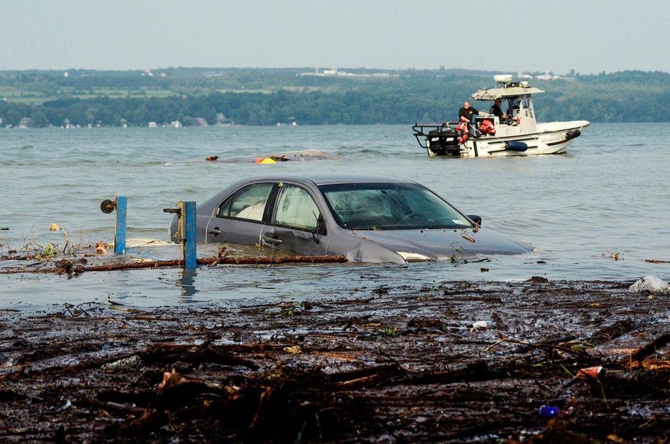 A car floats in Seneca Lake as crews