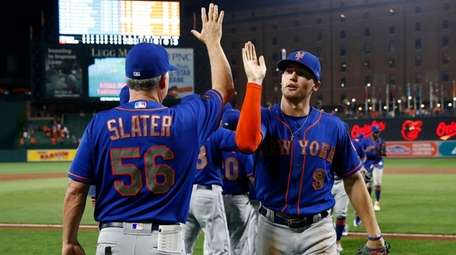 The Mets' Brandon Nimmo, right, high-fives assistant hitting