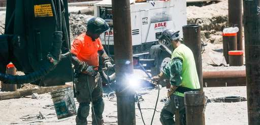 Construction workers welding on a jobsite in the