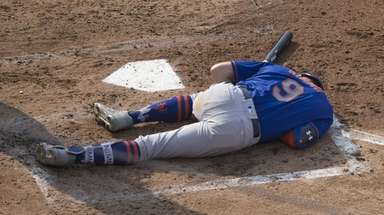 Mets' Brandon Nimmo lays on the ground after