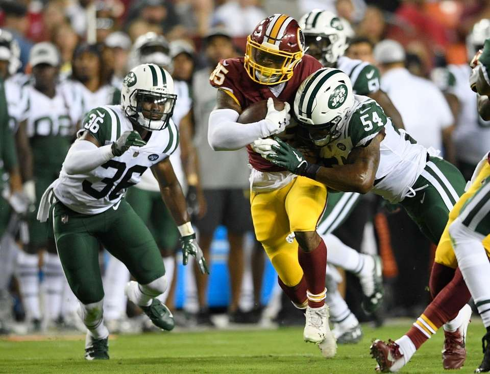 Redskins running back Kapri Bibbs, center, runs against