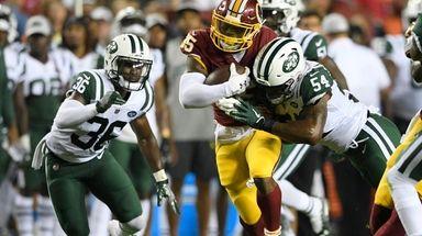 Redskins running back Kapri Bibbs, center, runs against