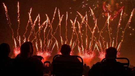 People watch as fireworks light the sky at