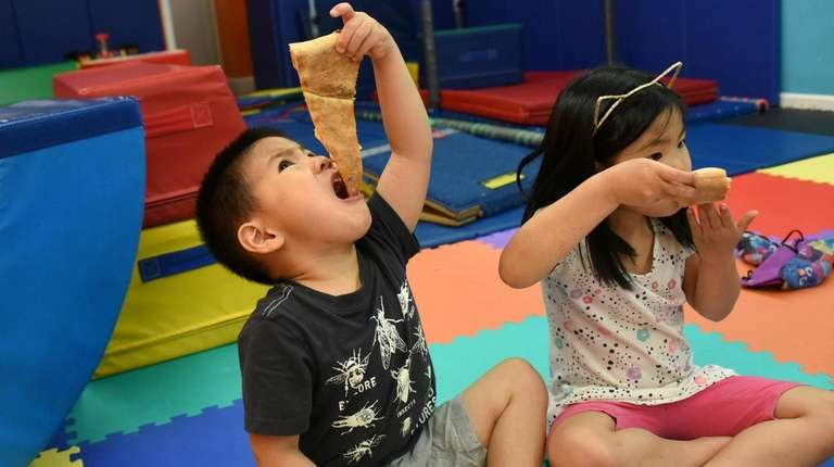 Siblings chow down during a program at Tumbling