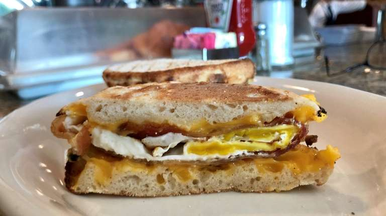 An egg sandwich with bacon and cheese is
