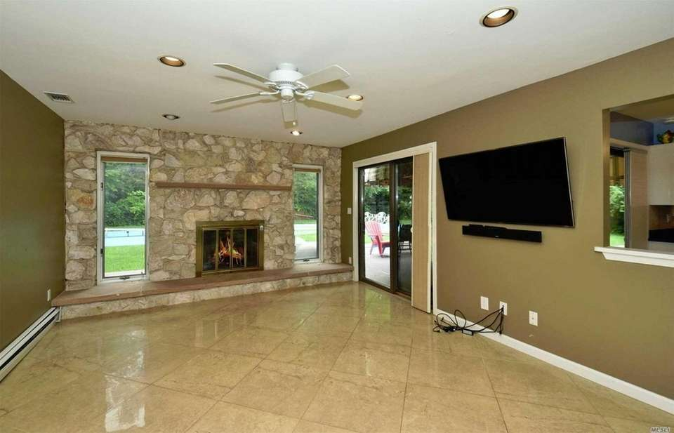 The family room features a stone fireplace flanked
