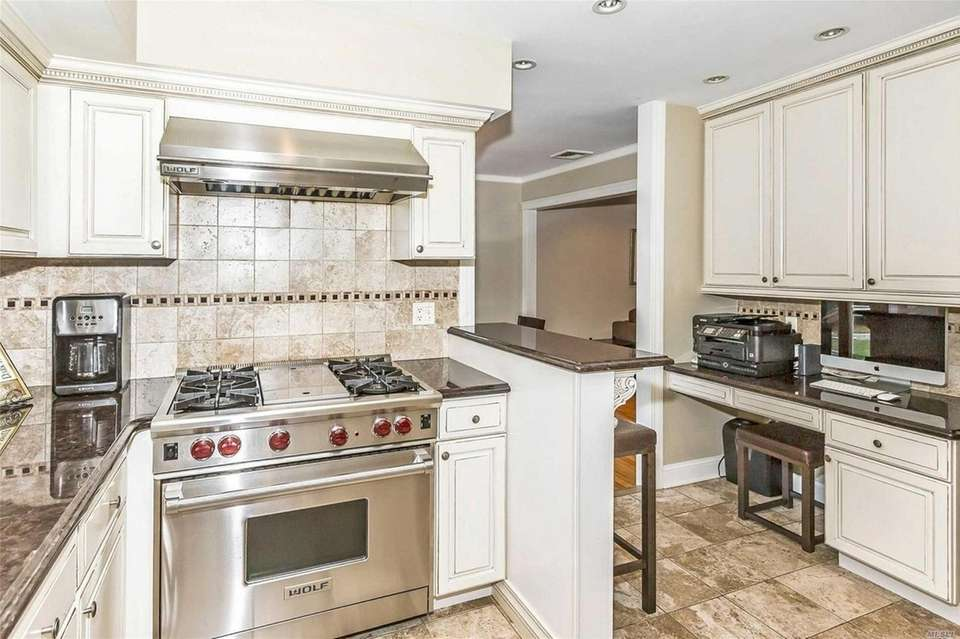The kitchen features white cabinetry and stainless steel