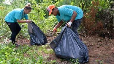 Stephanie Gonzalez, left, and Qiana Smith clean up