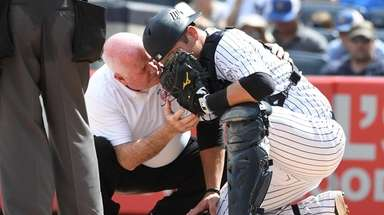 Yankees trainer Steve Donohue checks on Yankees catcher