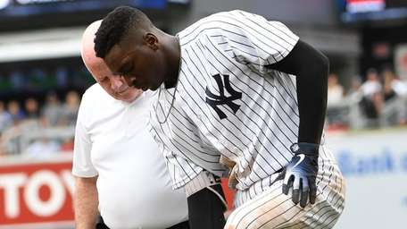 Yankees trainer Steve Donohue checks on shortstop Didi