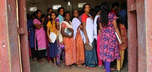 Women line up for food being distributed at
