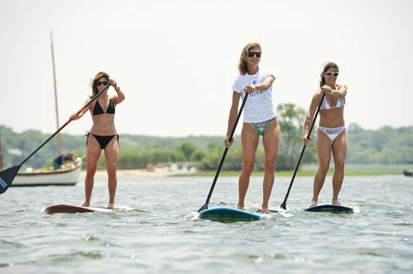 Gina Bradley, the owner of Paddle Diva, center,