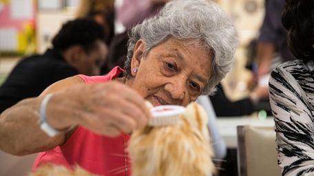 Aurora, 88, combs the hair of Bonita, a