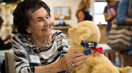 Helen, 84, interacts with Ace, a robotic dog