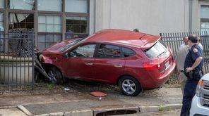 A car hit a fence, pushing a window