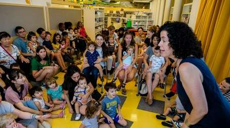Children's librarian Lesley Siegel entertains kids during Sing