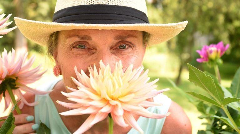 Kathy Burke poses with myriad varieties of dahlias