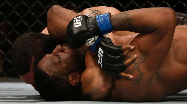 Cezar Ferreira, back, chokes Karl Roberson during their