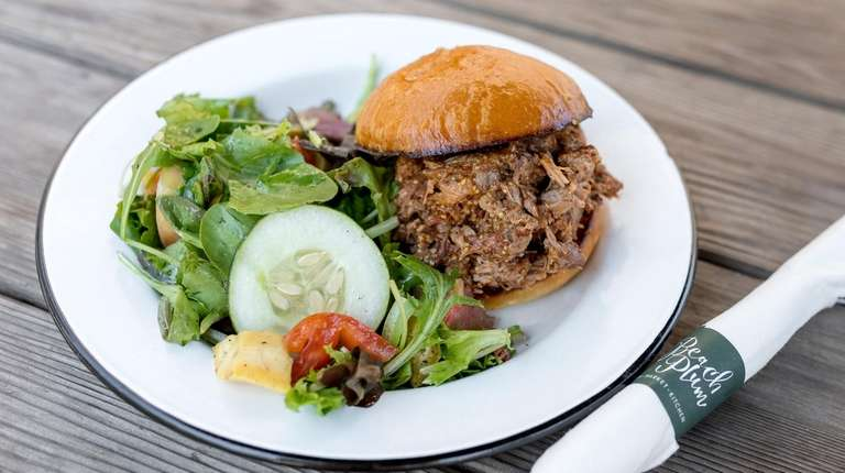 A barbecue pork sandwich with farm salad is
