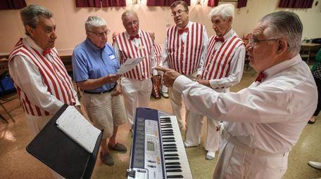 Long Island Harmonizers conductor Maurice Debar leads a