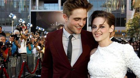 Robert Pattinson, left, and Kristen Stewart arrive at