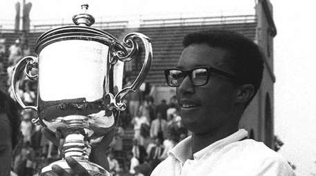 Arthur Ashe holds his trophy after defeating Tim