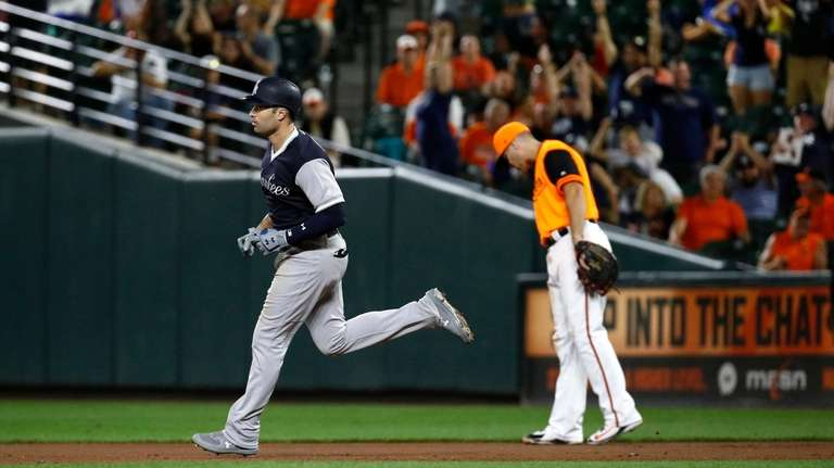 New York Yankees' Neil Walker, left, rounds the