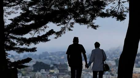 A man and woman walk under trees down
