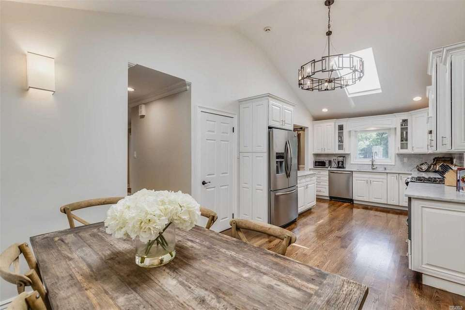 The renovated kitchen features wood floors, stainless steel
