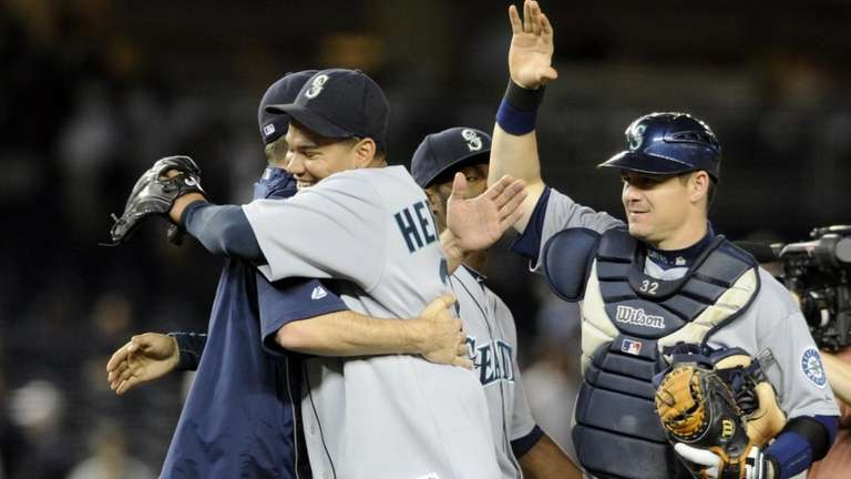 Felix Hernandez is hugged by a teammate after