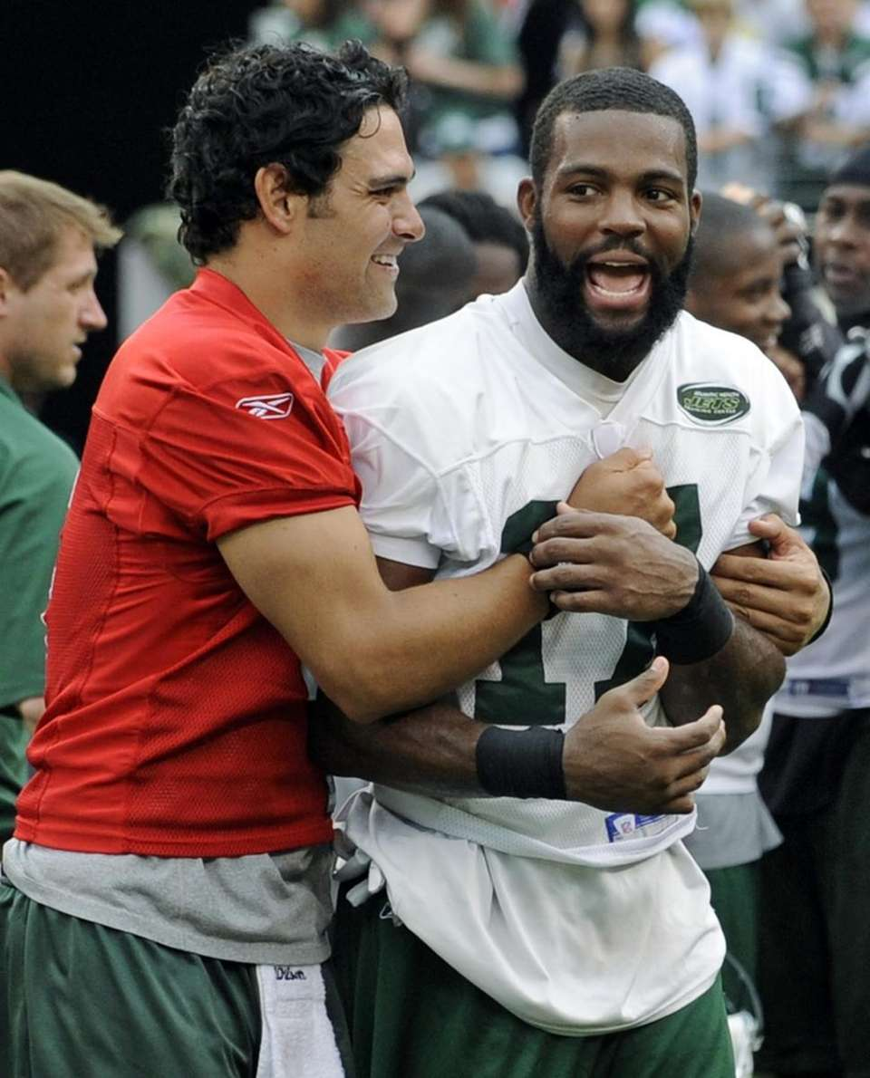 Jets quarterback Mark Sanchez, left, hugs wide receiver