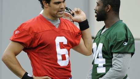 The Jets' Mark Sanchez, left, talks with cornerback