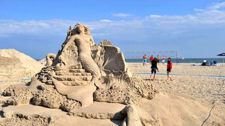 Volleyball players play behind a sand-sculpture in Long