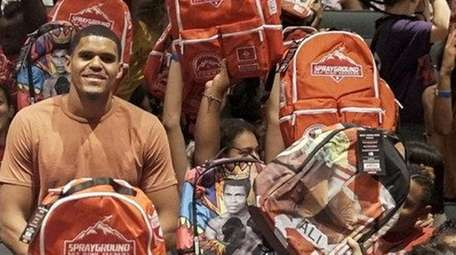 Tobias Harris handed out backpacks to children in