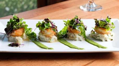 Pan-seared sea scallops are served atop potatoes with