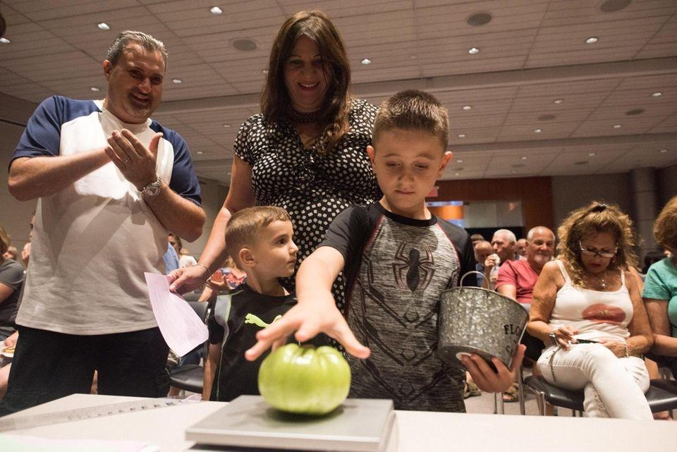 Antonio Turturiei, 6, of Shirley, weighs his tomato