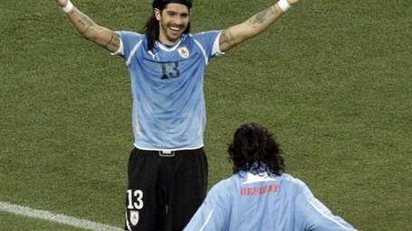 Uruguay's Sebastian Abreu, top, celebrates with a teammate